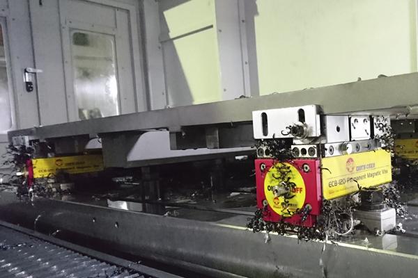close-up of magnetic vise blocks holding large flat metal sheet inside cnc machine