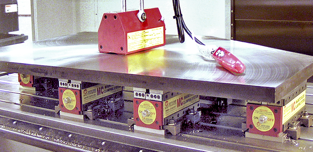Large flat metal sheet being held in place by techniks magnetic lifters and vise blocks